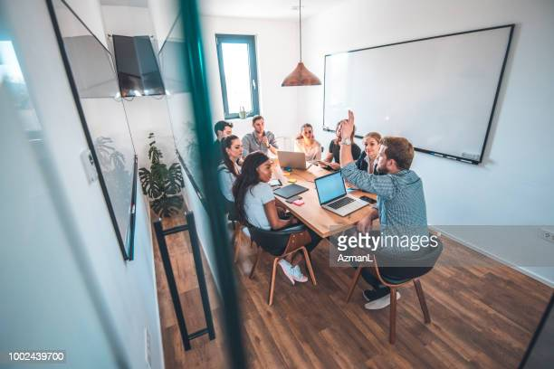 Colleagues discussing in board room during meeting