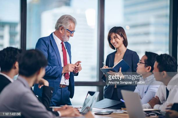 colleagues discussing in conference room - 数人 ストックフォトと画像