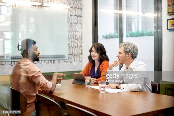 colleagues discussing in meeting at office - interview stock pictures, royalty-free photos & images