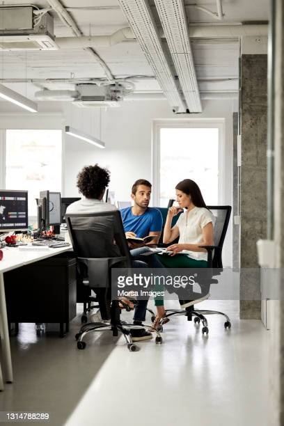 colleagues discussing in meeting at office - three people stock pictures, royalty-free photos & images