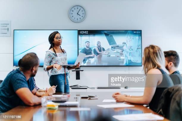 collega's bespreken in vergaderruimte tijdens videoconferentie - tonen stockfoto's en -beelden