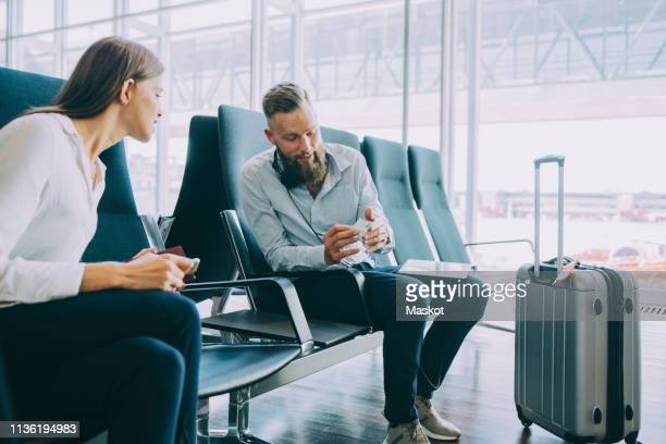 Colleagues discussing over business card while sitting in waiting room at airport
