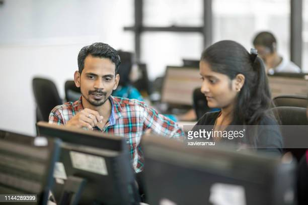 colleagues discussing over computer at office - india stock pictures, royalty-free photos & images