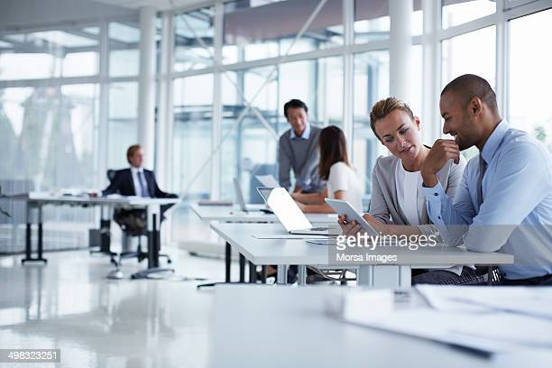 colleagues discussing over digital tablet - business stockfoto's en -beelden