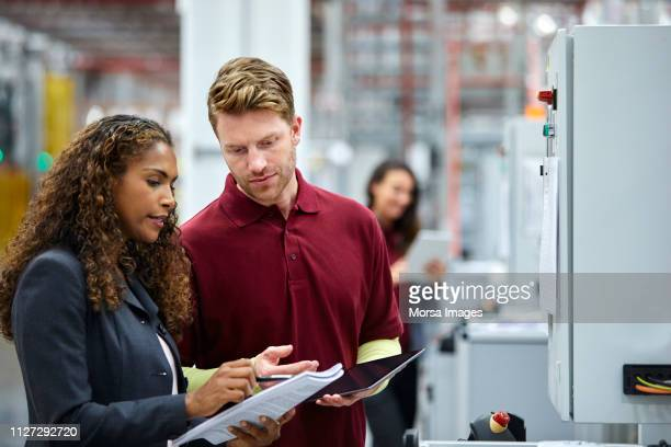colleagues discussing over documents in car plant - manager stock pictures, royalty-free photos & images