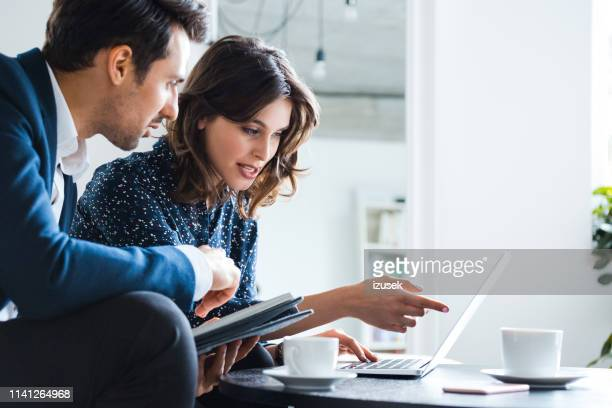 colleagues discussing over laptop at workplace - businesswoman stock pictures, royalty-free photos & images