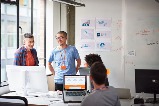 Colleagues discussing plan in tech start-up office - gettyimageskorea
