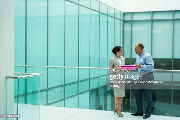 Colleagues discussing project on atrium balcony
