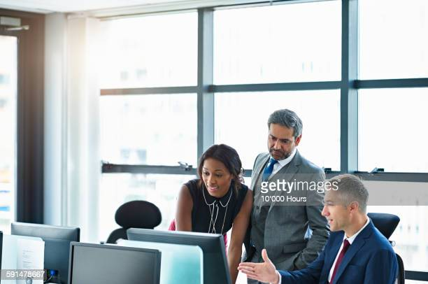 colleagues discussing project on computer screen - businesswear stock pictures, royalty-free photos & images