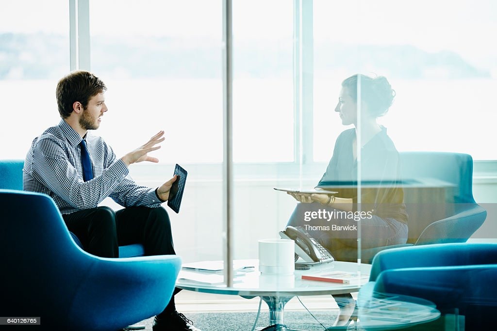 Colleagues discussing project on digital tablets : Stock Photo