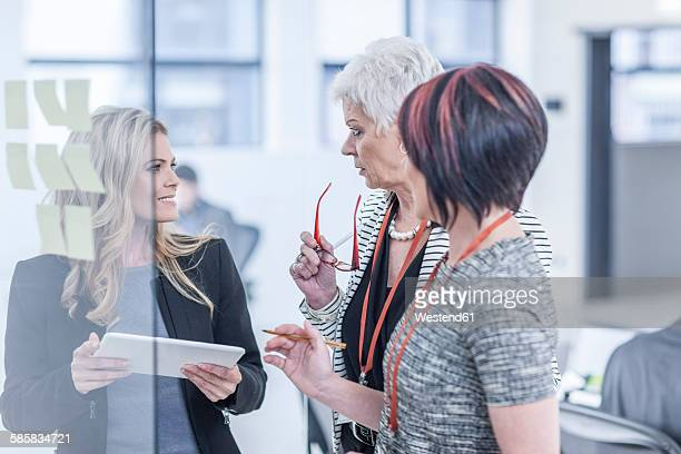 Colleagues discussing sticky notes on glass screen