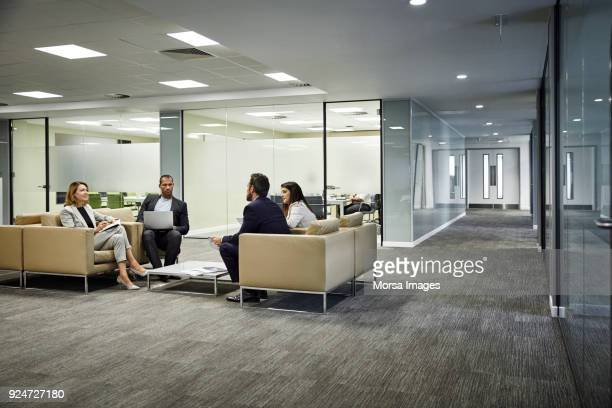 colleagues discussing strategy in lobby at office - hotel lobby stock pictures, royalty-free photos & images