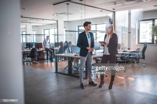 colleagues discussing while standing at workplace - office partition stock pictures, royalty-free photos & images