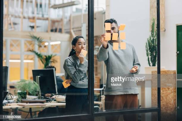 colleagues discussing while sticking adhesive notes on glass wall in office - nieuw bedrijf stockfoto's en -beelden