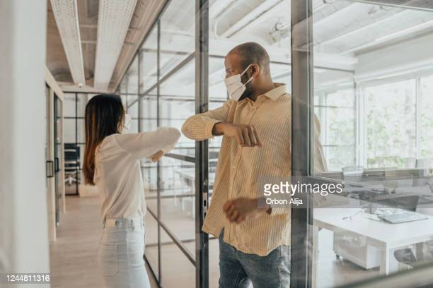 colleagues doing alternative greeting during covid-19 - elbow bump stock pictures, royalty-free photos & images