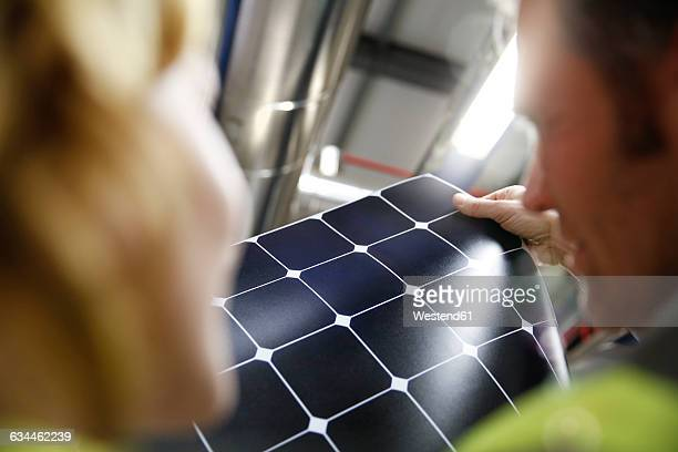 Colleagues examining innovative solar panel