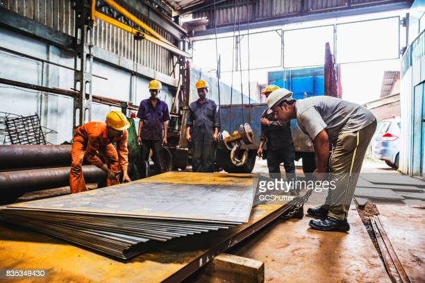 colleagues examining the stacks of sheet metal to decide on the kind of chain required for lifting - sheet metal stock pictures, royalty-free photos & images