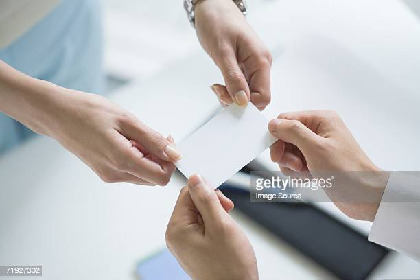 colleagues exchanging a business card - business cards stock photos and pictures