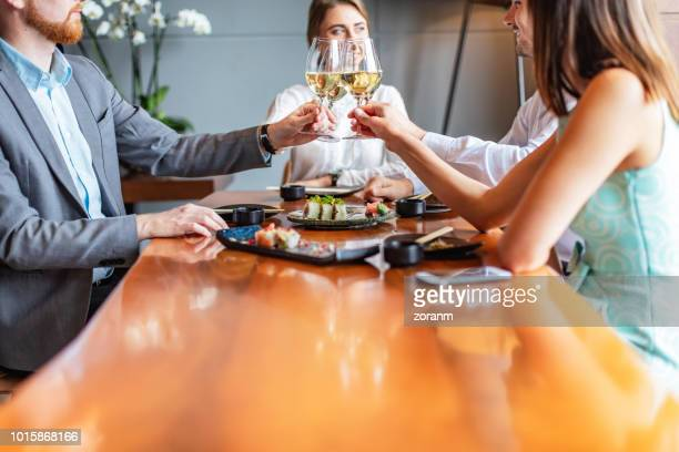 colleagues giving a toast at lunch - sushi restaurant stock photos and pictures