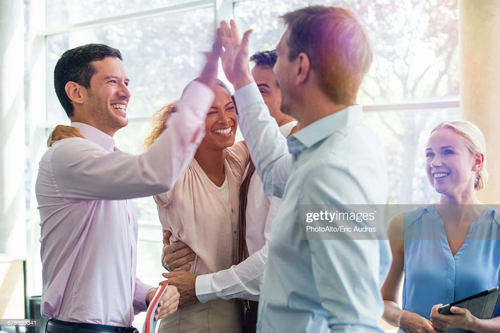 Colleagues giving each other high-five : Stock Photo