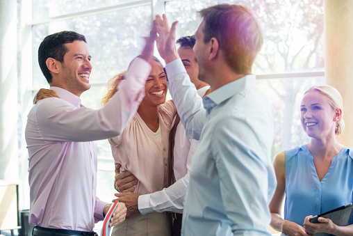 Colleagues giving each other high-five - gettyimageskorea