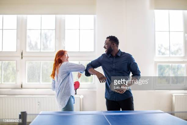colleagues giving elbow bump while playing table tennis in office - fun stock pictures, royalty-free photos & images