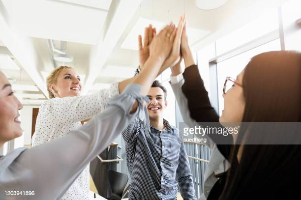 colleagues giving high five in office - high five stock-fotos und bilder