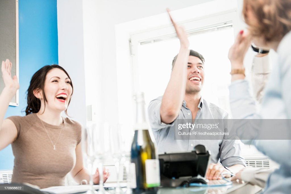 Colleagues giving high fives in office, champagne on table : Stock Photo