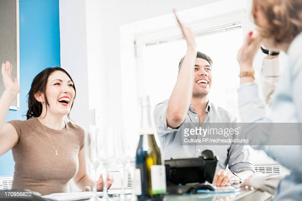 Colleagues giving high fives in office, champagne on table