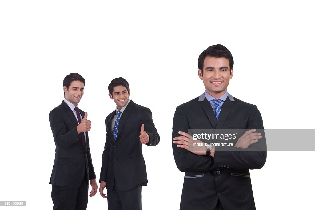 Colleagues giving thumbs up to fellow businessman : Stock Photo