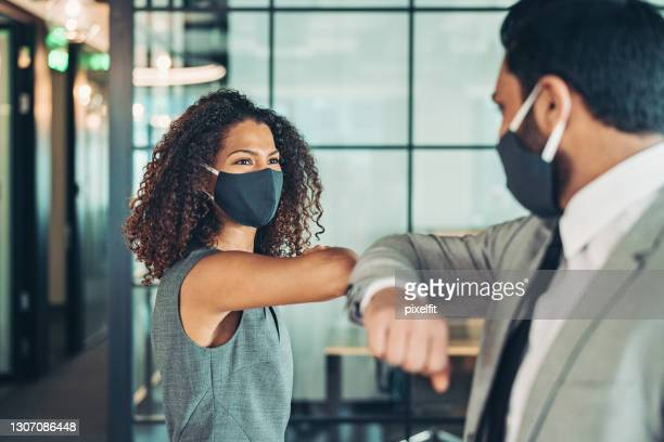 colleagues greet in the office during the covid-19 pandemic - avoidance stock pictures, royalty-free photos & images
