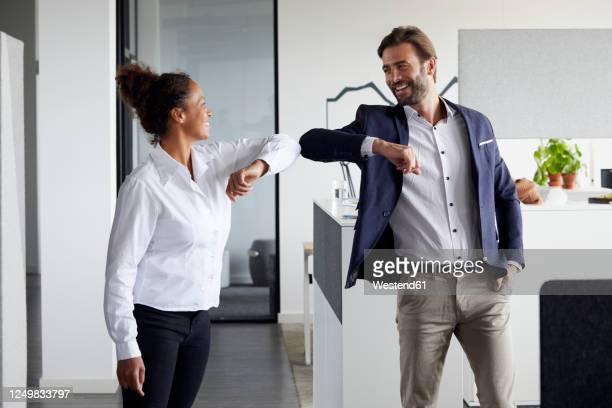 colleagues greeting each other in office during corona crisis - greeting stock pictures, royalty-free photos & images
