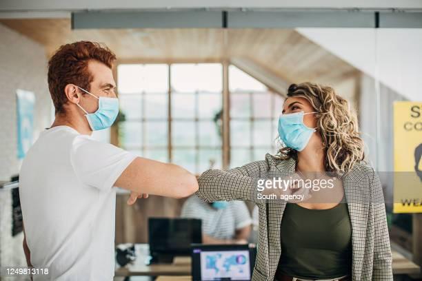 collègues se saluant avec les coudes dans le bureau pendant la pandémie de covide-19 - éviter de se serrer la main photos et images de collection