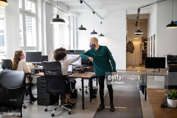 colleagues greeting with elbow bump in office - greeting stock-fotos und bilder