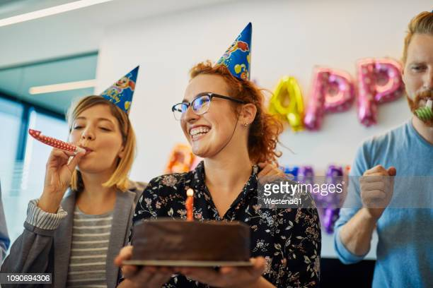 colleagues having a birthday celebration in office with cake, party blower and party hats - birthday party stock pictures, royalty-free photos & images