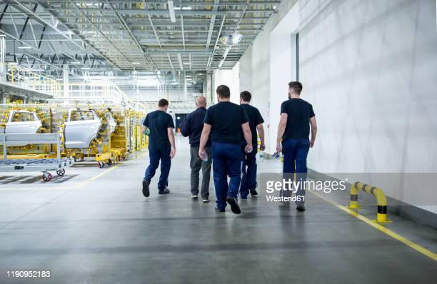 colleagues having a break and walking in a modern car factory - industrieberuf stock-fotos und bilder
