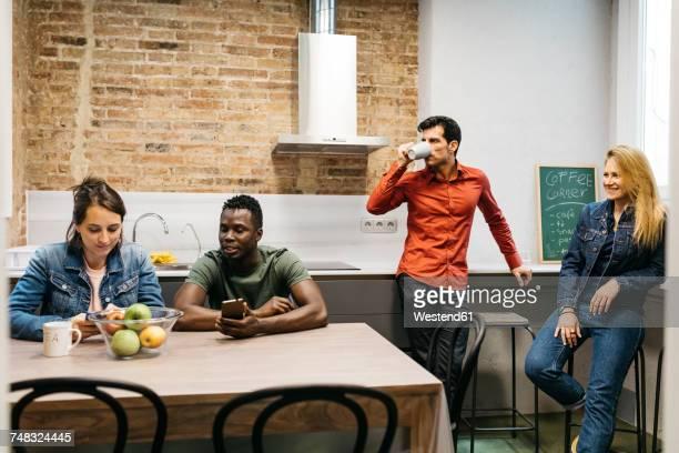 Colleagues having a break in office kitchen