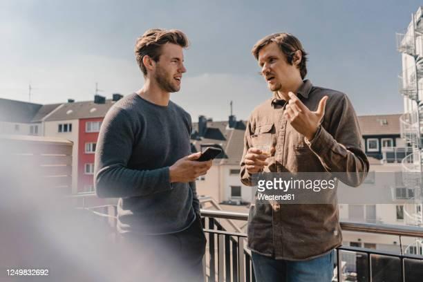 colleagues having a break on the balcony, talking, using smartphone - tre fjärdedels längd bildbanksfoton och bilder