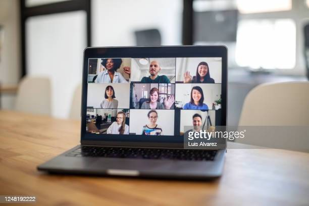 colleagues having a work meeting through a video call - videoconferenza foto e immagini stock