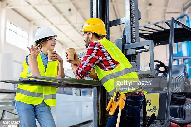 Colleagues having coffee break in factory