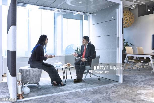 Colleagues having meeting in glass pod in office
