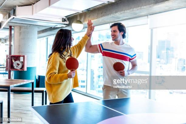 colleagues high-fiving at the table tennis match - doubles sports competition format stock pictures, royalty-free photos & images