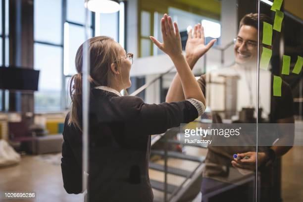 hög fiving kollegor på jobbet - high five bildbanksfoton och bilder