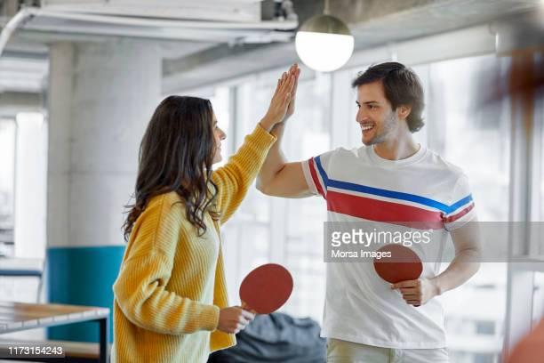 colleghi ad alto fiving mentre giocano a ping pong - doppio foto e immagini stock