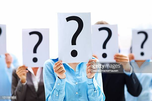 colleagues holding question mark signs in front of their faces - five people stock pictures, royalty-free photos & images