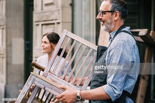 colleagues holding wooden chairs while standing outside antique shop - carrying stock pictures, royalty-free photos & images