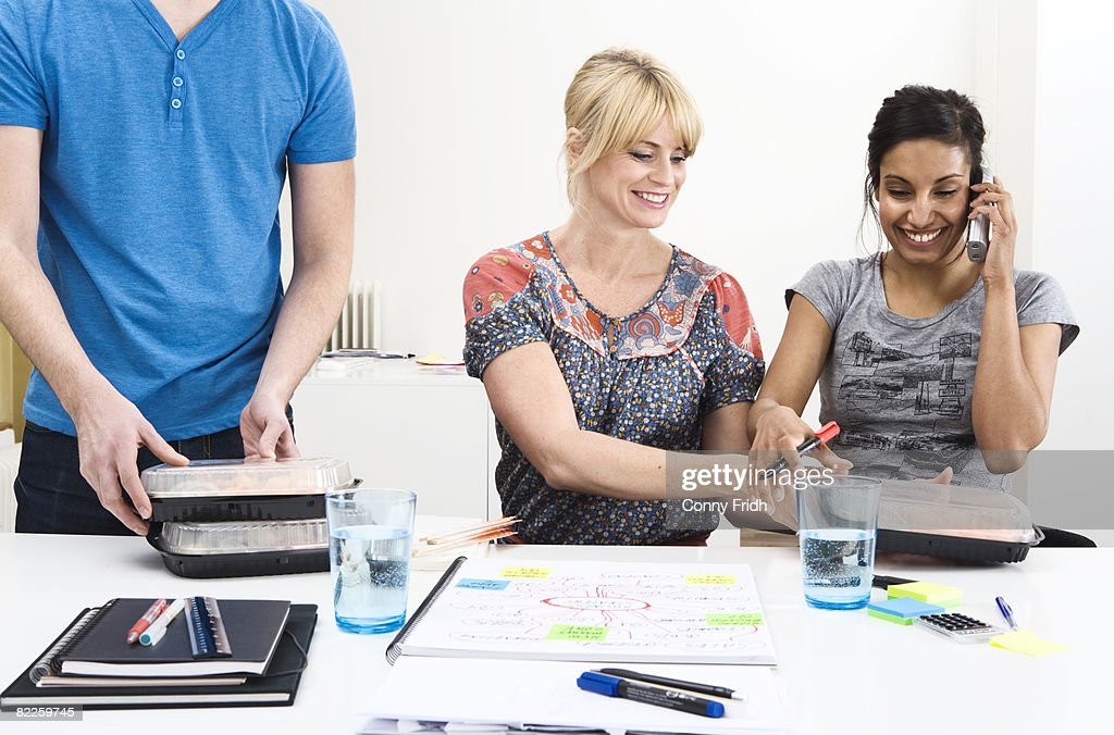 Colleagues in an office having sushi for lunch Sweden. : Stock Photo