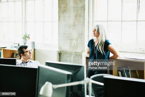 Colleagues in discussion at workstation in design office