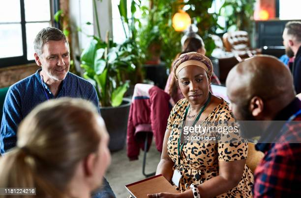 colleagues in group workshop session in cafe - black ethnicity stock pictures, royalty-free photos & images
