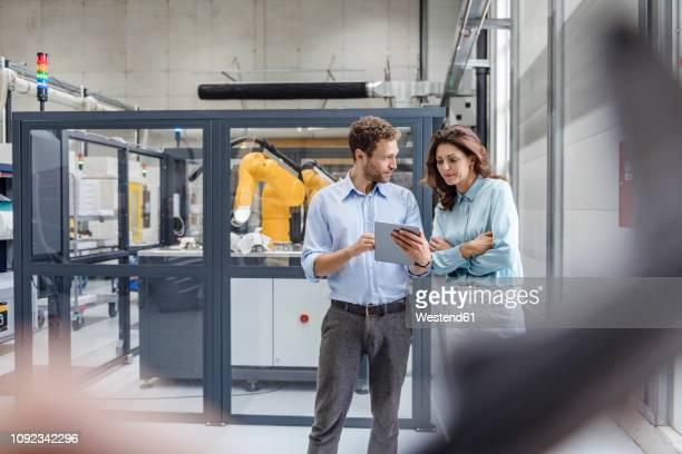 colleagues in high tech company controlling industrial robots, using digital tablet - herstellendes gewerbe stock-fotos und bilder